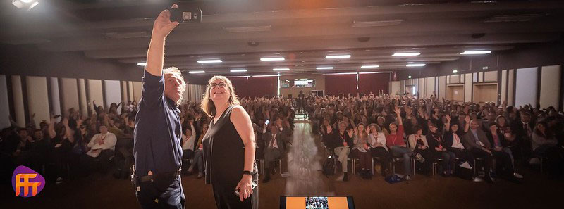A photo of Beth and a gentleman taking a selfie in front of a large audience.